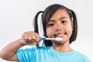 Little girl brushing her teeth in studio shot photo