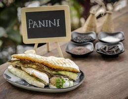 Vegan roasted vegetable toasted panini sandwich in rustic garden table setting outdoors in Sicily photo
