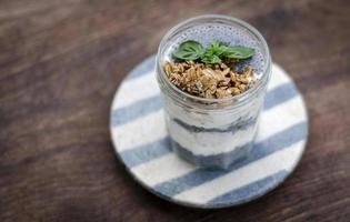 Yogur rústico saludable casero y granola con semillas de albahaca taza de merienda para el desayuno foto