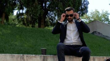 Man with A Beard in A Classic Suit Puts on Sunglasses video