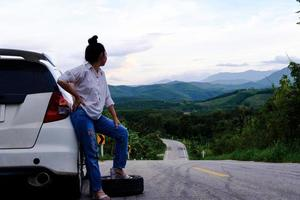 Young Asian woman sanding near the car waiting for help photo