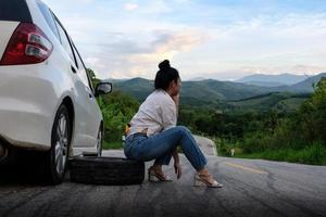 Young Asian woman siting near the car waiting for help photo