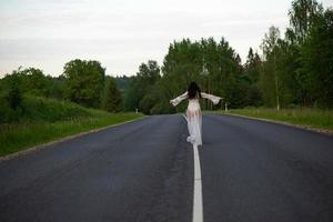 Rear view of a young woman standing on an empty asphalt country road photo