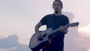 Guy Plays on Acoustic Guitar in Summer Fields video