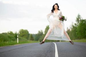 Funny young woman in white dress jumping on empty asphalt road photo