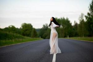 Woman in white dress spinning on empty road photo