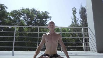 Male with Tattoos Does Yoga Exercises video