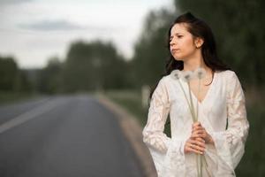 Portrait of young brunette woman with dandelion on rural asphalt road photo