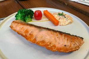 Grilled salmon steak with vegetable garnishing photo