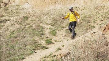 jeune homme avec un sac à dos courant dans les montagnes video