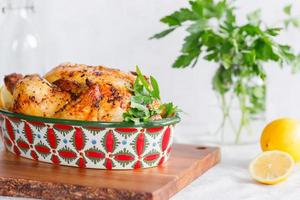 Whole roasted chicken with fresh parsley and lemon photo