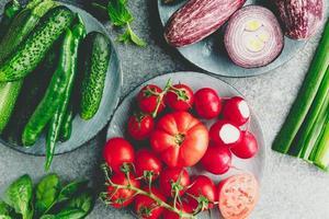 tomates y diferentes verduras frescas en una mesa foto