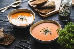 Vegetable creamy healthy soup with pumpkin seeds on a kitchen table photo