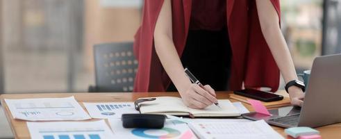 Mujer de negocios que trabaja en la oficina con un portátil y documentos en su escritorio foto
