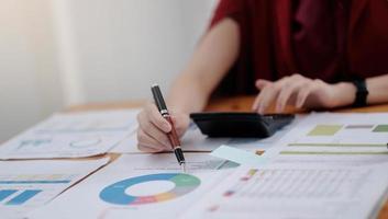 Mujer contable use calculadora y computadora con lápiz de sujeción en el escritorio foto