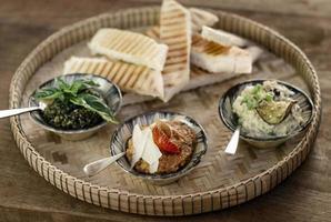Plato de tapas de aperitivo mezze turco vegetariano en la mesa de restaurante de madera rústica foto