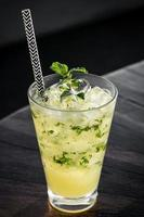 Orange mojito summer cocktail drink on outdoor riverside bar table photo