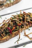 Spicy dried squid and roast vegetables toasted open sandwich tapas snack in Portugal photo