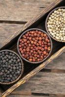 Organic Kampot white red and black peppercorns in natural rustic style wood display in Cambodia photo