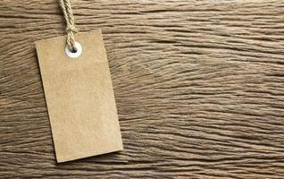 Blank tag tied on wooden background photo