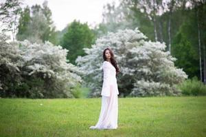retrato, de, un, hermoso, mujer joven, en el parque, en, florecer, ramas foto