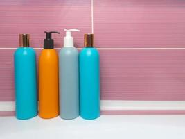 Plastic bottles of various colors with detergent, shower gel, shampoo photo