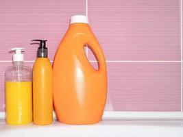 Three plastic bottles of detergent, shower gel, shampoo on the bathtub photo