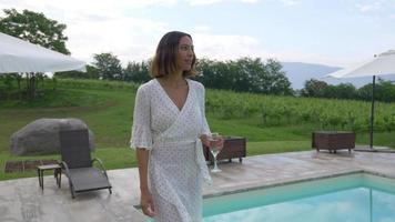 una mujer caminando con una copa de vino blanco en una piscina video