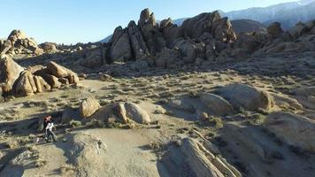 Aerial shot of a young man with his dog in a mountainous desert. video