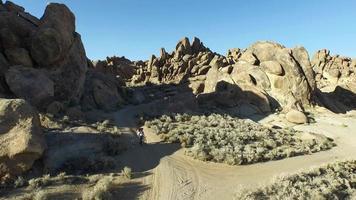 homme sac à dos avec son chien sur un chemin de terre dans un désert montagneux. video