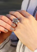 Flower form silver ring on a finger. Interesting jewelry design photo