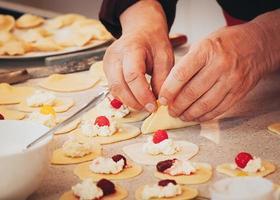 manos preparando albóndigas de queso y cereza foto