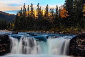 amanecer sobre las cataratas del río ovejas en movimiento rápido foto