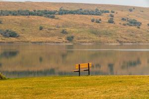 Picnic tables and bench sit alone by waters edge photo