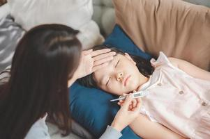 Sick Asian girl daughter sleeping on the couch photo