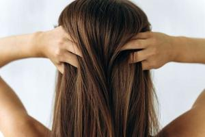 young girl touching to her hair and runs fingers through the hair photo