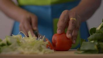 Woman cutting tomato on wooden cutting board for healthy food. video