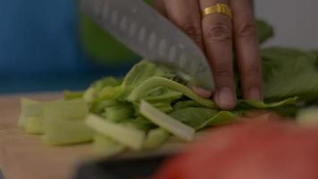 Woman cutting Chinese Cabbage on wooden cutting board before cooking. video