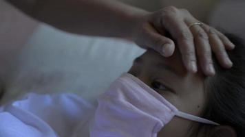 Hand of mother touch her sick daughter's forehead gently at home. video