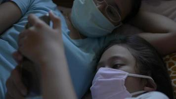 Daughter wears face mask using mobile phone laying on the bed with mom video