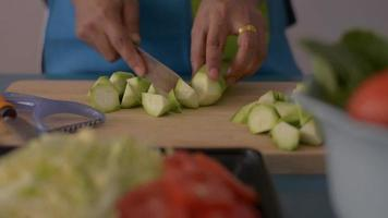 Woman cutting angled loofah on wooden cutting board in the kitchen. video
