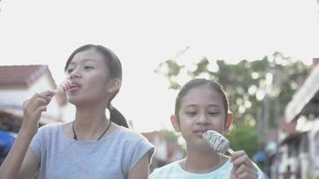 Two girls enjoy eating ice cream while walking together on the path. video
