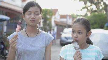 Pretty girl and her sister enjoy eating ice cream on the footpath. video