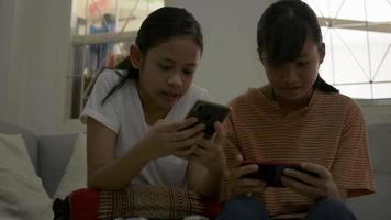 Two sisters enjoy to play games on mobile smart phone at home. video