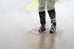mujer jugando bajo la lluvia, saltando en charcos con salpicaduras foto