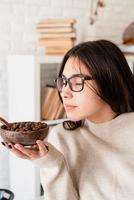 Mujer preparando café en una cafetera, oliendo granos de café foto