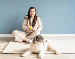 Bella mujer con perro de raza mixta jugando a la pelota en casa foto