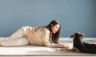 Bella mujer con perro juguetón abrazando en casa foto