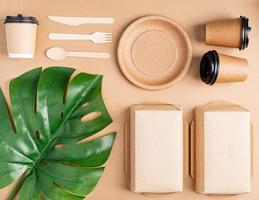 Eco friendly disposable tableware on brown background photo