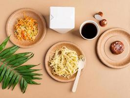 Eco friendly disposable tableware full of food on brown background photo